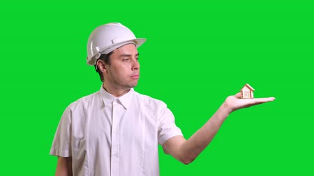 miniatűr : Young male engineer standing and showing hand palm with small model of house on green screen background