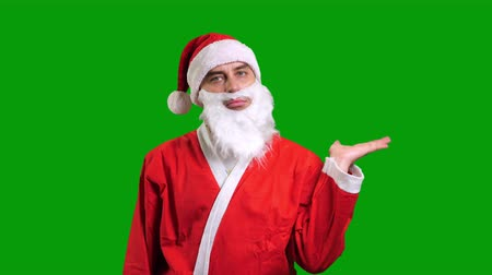 knipoog : Santa Claus in red suit showing hand palm on green chroma key background Stockvideo