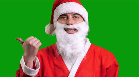 knipoog : Santa Claus in red suit pointing aside on green chroma key background