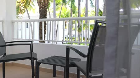 veranda : Tropical view on garden with palm trees from hotel balcony with table and chairs