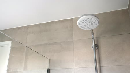 кафельный : Shower head at tiled bathroom interior