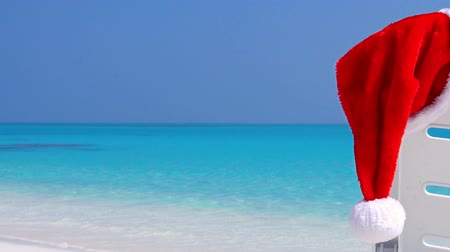 longer : Santa Claus Hat on sunbed near tropical calm beach with turquoise sea water and white sand
