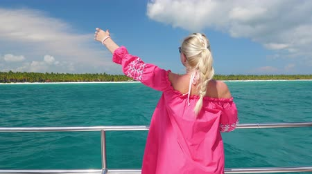 регата : Young blond woman in pink dress and sunglasses on catamaran yacht Стоковые видеозаписи
