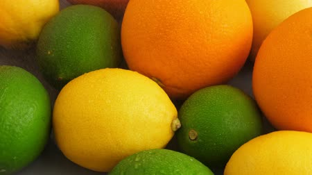 cítrico : Half cut juicy lime on citrus fruit background, a lot of lemon, oranges and limes top view Vídeos