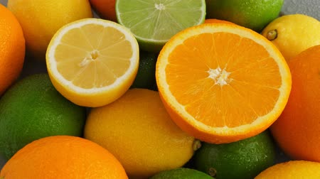 césar : Half cut juicy lime on citrus fruit background, a lot of lemon, oranges and limes top view Stock Footage