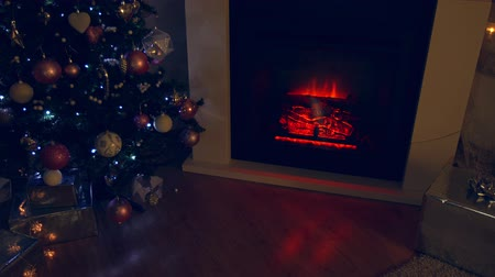 christmas tree with lights : New year and Christmas celebration near fireplace in cozy room Stock Footage