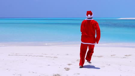 svolazzi : Man in Santa Claus Hat walking along beach and wag hands