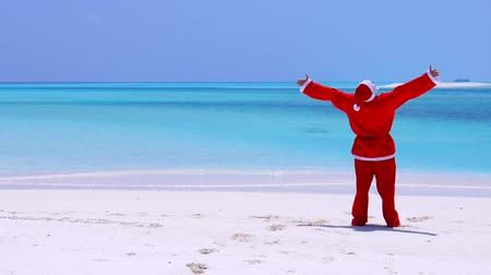 new clothes : Man in Santa Claus Hat walking along beach and wag hands