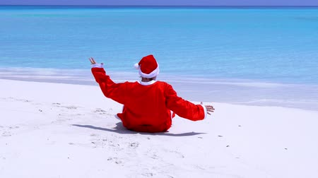 traje de passeio : Man in Santa Claus Hat walking along beach and sitting down on sand