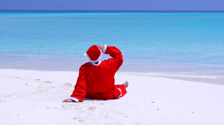 uzanmış : Man in Santa Claus Hat sitting with outstretched hands on sandy beach