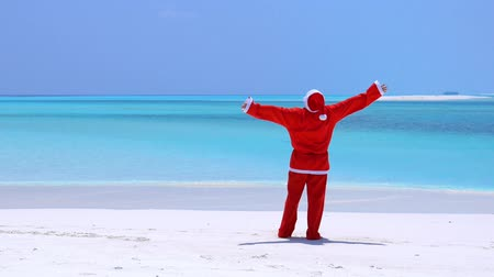 traje de passeio : Man in Santa Claus Hat walking along beach and wag hands
