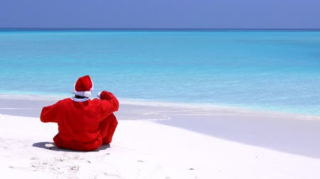 new clothes : Man in Santa Claus Hat walking along beach and sitting down on sand