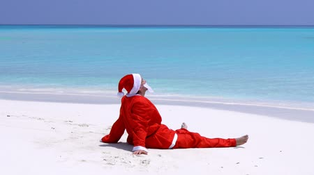 vízpart : Man in Santa Claus Hat sitting and wag hands on sandy beach Stock mozgókép