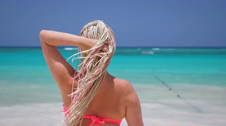 blue braid : Woman with african braids in pink bikini on tropical beach with turquoise sea water Stock Footage