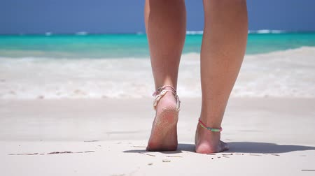 lépések : Woman standing on sandy beach with turquoise sea water. Female legs walk into the sea with waves
