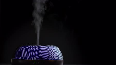 inhalacja : Diffuser for essential oils diffusing steam on black background