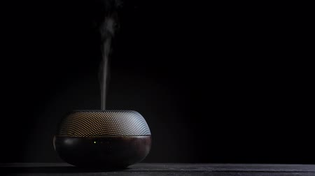 diffuse : Diffuser for essential oils diffusing steam on black background