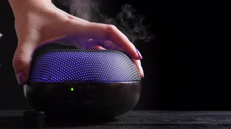 diffuse : Woman add essential oil into Diffuser on black wooden table