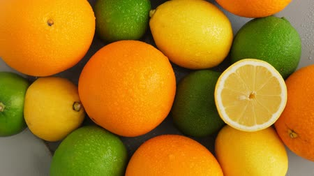 vitamine c : Half cut juicy lime on citrus fruit background, a lot of lemon, oranges and limes top view Stockvideo