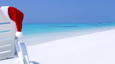 deck chairs : Santa Claus Hat on sunbed near tropical calm beach with turquoise sea water and white sand