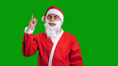 Santa Claus in red suit pointing up on green chroma key background