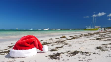Christmas Santa Claus hat on tropical sandy beach with calm waves Stock Footage