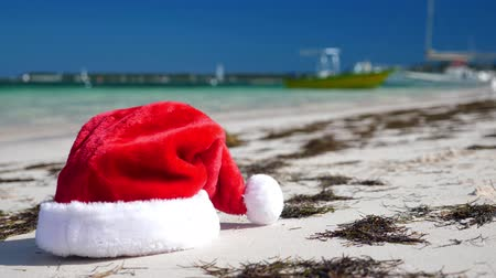 Christmas Santa Claus hat on tropical sandy beach with calm waves Stockvideo
