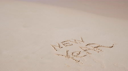 escrito : Word NEW YEAR written on sand close to sea waves Stock Footage