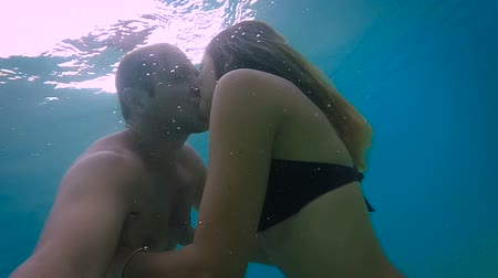 fundo : Sweet couple kissing under the water in the ocean (slow motion)