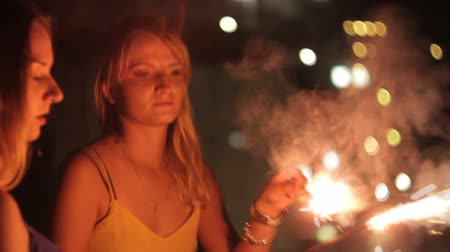 hipster : Young girl dancing with sparklers in their hands on the roof Stock Footage