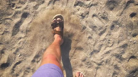 step : A man walks in flip flops on the sand near the sea (slow motion)