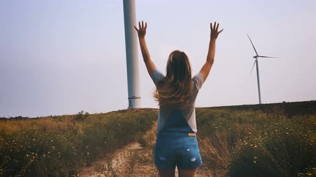 parque eólico : Happy girl running towards the wind turbine, slow motion.