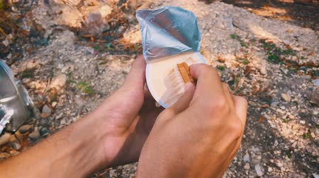 salya : A hungry man in camping smears cream on biscuits. Slow motion. Stok Video