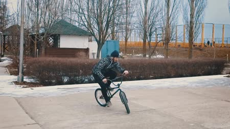 sporty zimowe : Teenager rides the BMX and does tricks and jumps in the winter park. Slow motion. 120 fps. Wideo