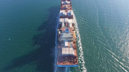 oceano : Aerial view of container ship passes through the channel goes into the open ocean after loading in the port of China at full speed. 4K.