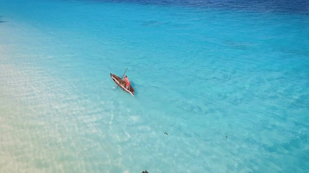 takımadalar : Aerial view of a poor fisherman with a torn shirt sails on a small boat on clear blue water along a tropical beach with beautiful hotels in Africa. Indian Ocean. Zanzibar. 2017