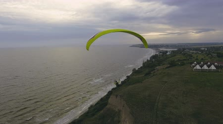 Paraplane, paraglider in the air aerial shot. Extreme man flies on a paraglider over a cliff near the sea. Extreme life.