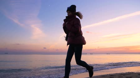 Beautiful happy young girl in warm clothes runs along the beach towards the beautiful sunset and jumps, enjoying life in slow motion. Girl model.