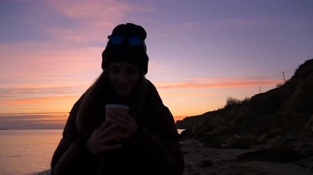 A beautiful happy young girl in warm clothes walks along the beach towards a beautiful sunset and drinks warm coffee, enjoying life in slow motion. Girl model. Stok Video