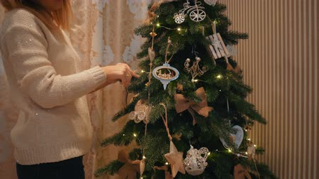 A beautiful blond girl in a white woolen sweater dresses up a Christmas tree in a cozy house with a warm atmosphere. New Years Eve.