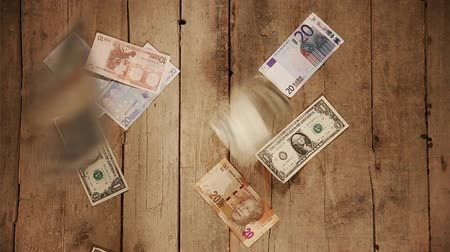 finanças : moneyrain with a lot of currencies on a wooden background