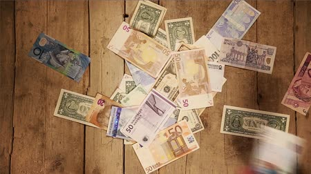 finansman : lot of currencies are taken by many hands on a wooden background Stok Video