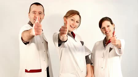 hemşirelik : three care giver in front of white, lifting their thumbs up