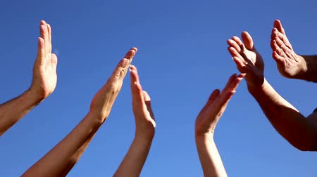 person's hand : Clapping hands from three persons in front of a blue sky