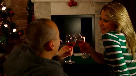 kırmızı şarap : couple drinking wine in front of an chimney Stok Video