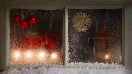 nevando : christmas decoration behind a window with continue snowing