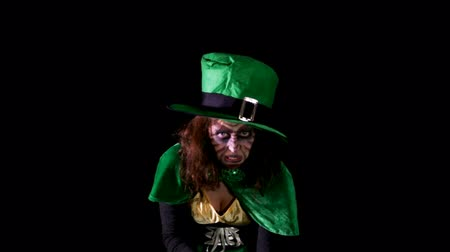 pagan feast : spooky leprechaun is luring the viewer, black background, hd video Stock Footage