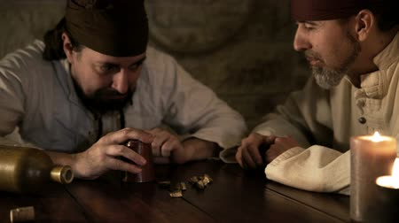 средневековый : Two pirates are playing with dices, One of Them is a Sore Loser, pushing the head of the winner on the table Стоковые видеозаписи