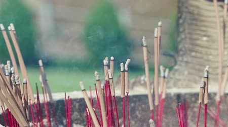 floating smoke from red wood incense stick for worship the Buddha in Asian culture footage. Wideo