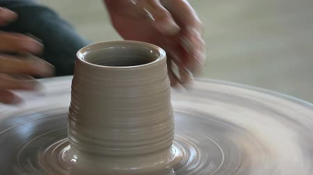 a teacher holding a small hand of a kid to helps and teaching how to make a vase pottery workshop together.